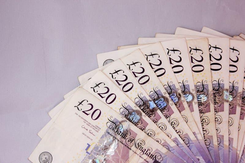 De Engelse van geldponden contante betalingen betalen verdienen van het het toerisme scads broodje van het munt20pounds inkomen v stock afbeelding