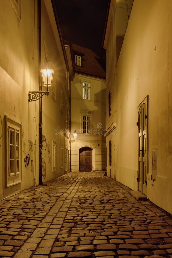 De engte cobbled straat in oude middeleeuwse stad met verlichte huizen stock foto's
