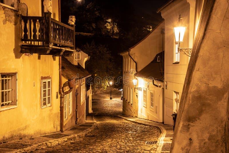De engte cobbled straat in oude middeleeuwse stad met verlichte huizen door uitstekende straatlantaarns, Novy svet, Tsjechisch Pr stock afbeeldingen