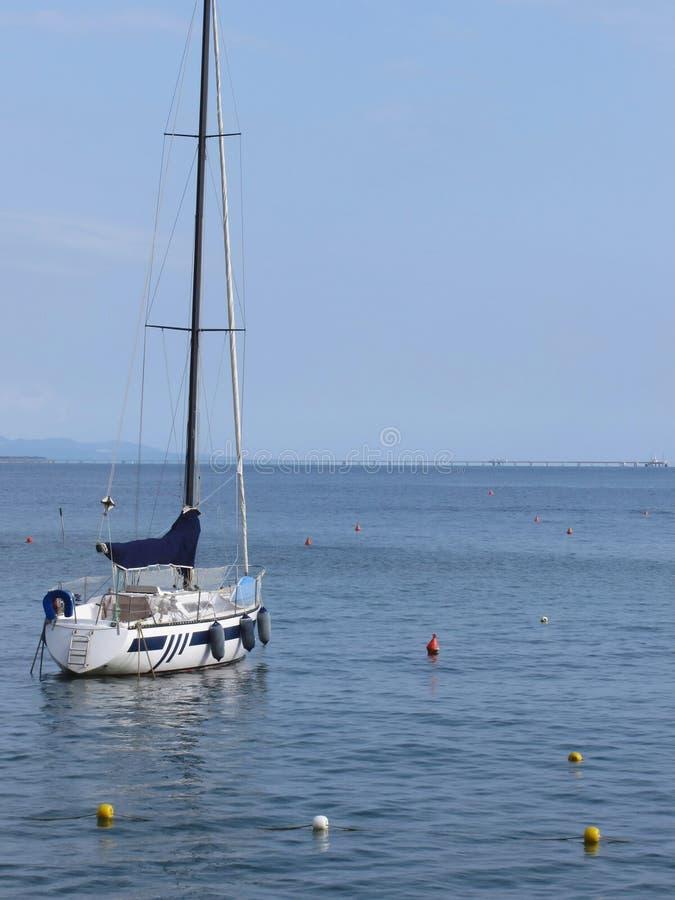 De enige zeilboot ligt bij anker in een haven wachtend op de wind te verschuiven Toscanië, Italië royalty-vrije stock foto