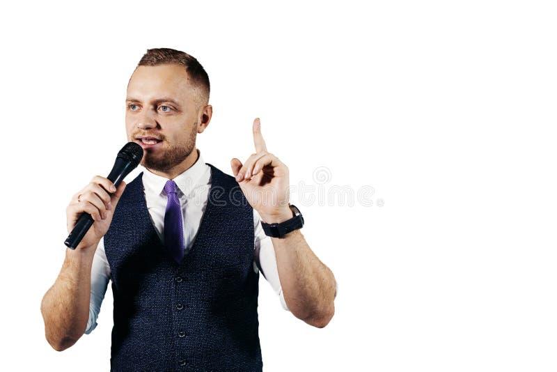 De entertainer De jonge elegante sprekende die microfoon van de mensenholding, op witte achtergrond wordt geïsoleerd stock fotografie
