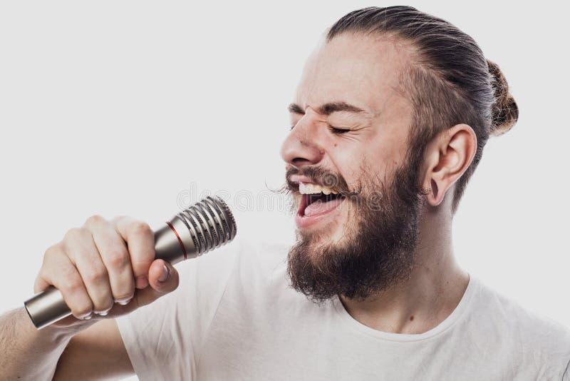 De entertainer De jonge sprekende die microfoon van de mensenholding, op witte achtergrond wordt geïsoleerd royalty-vrije stock afbeelding