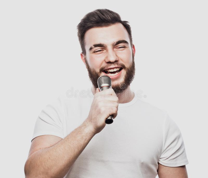 De entertainer De jonge sprekende die microfoon van de mensenholding, op witte achtergrond wordt geïsoleerd royalty-vrije stock afbeeldingen