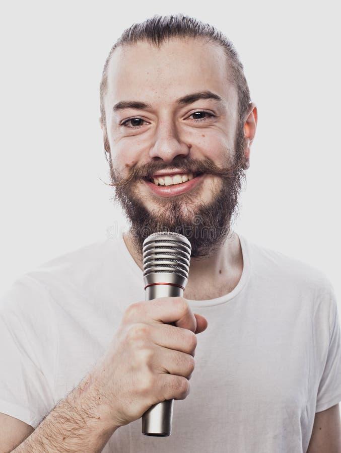 De entertainer De jonge sprekende die microfoon van de mensenholding, op witte achtergrond wordt geïsoleerd royalty-vrije stock fotografie