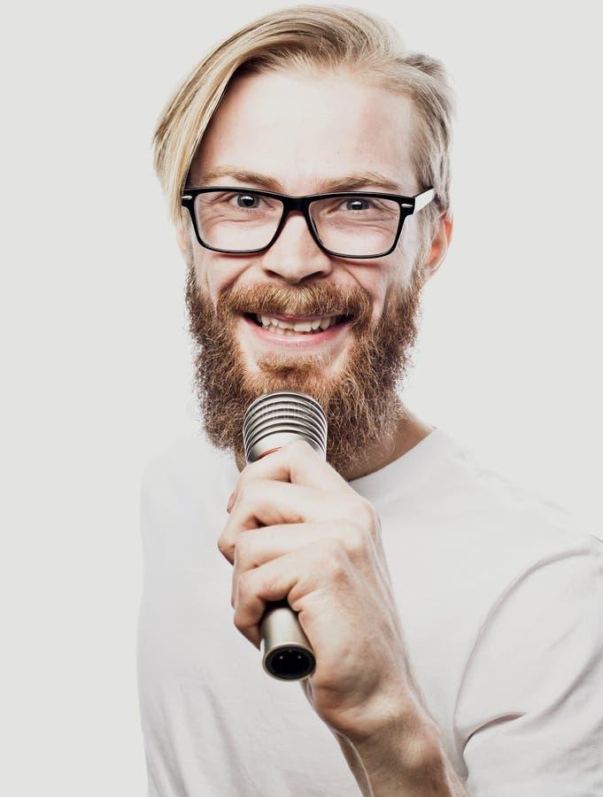 De entertainer De jonge sprekende die microfoon van de mensenholding, op witte achtergrond wordt geïsoleerd stock foto's