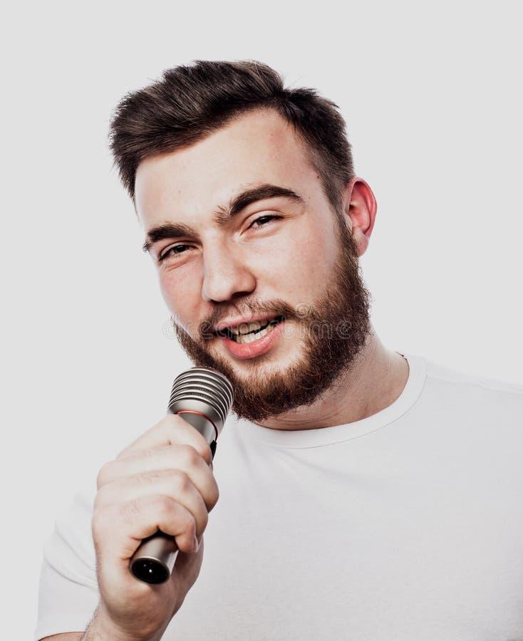 De entertainer De jonge sprekende die microfoon van de mensenholding, op witte achtergrond wordt geïsoleerd royalty-vrije stock foto's