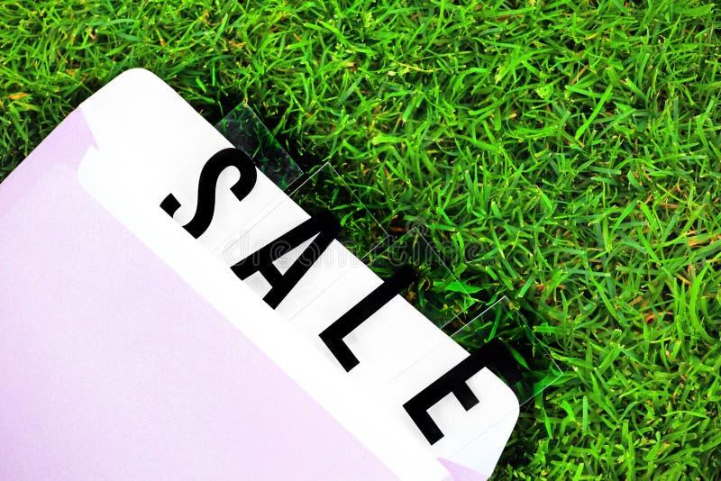 De envelop groen gras van de verkooptekst stock fotografie