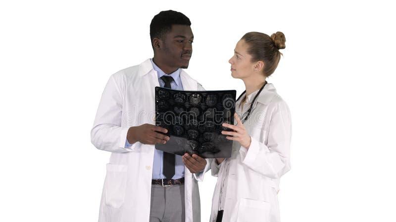 De ernstige aardige vrouw arts en afro Amerikaanse arts studiehersenen lichten op witte achtergrond door royalty-vrije stock foto's