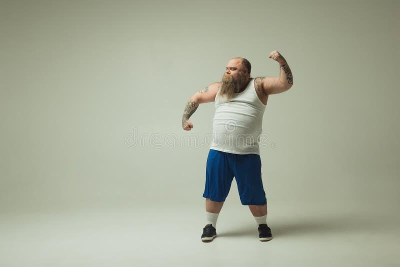 De ernstige dikke mens schept van zijn lichaam op stock afbeelding