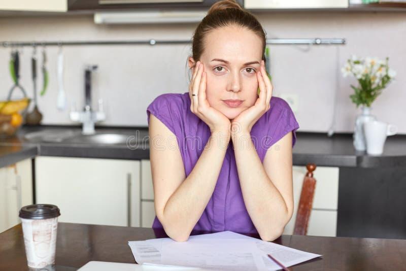 De ernstige donkere haired jonge huisvrouw werkt freelance, houdt handen op wangen, werkt met document documenten, drank beschikb stock afbeeldingen