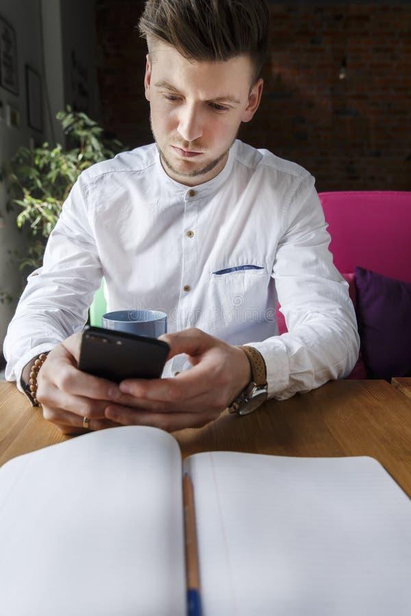 De ernstige en geconcentreerde mens zit bij lijst en kijkt op de telefoon Er is een dagboek liggend op de lijstmens dichtbij zit stock foto's