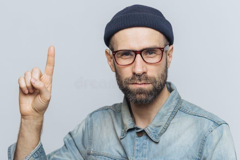 De ernstige gebaarde mens draagt glazen, modieuze hoed en het denimjasje, heft voorvinger op zoals probeert om u over iets te waa stock foto
