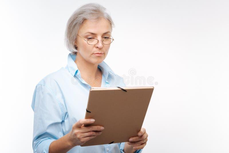 De ernstige grijs-haired documenten van de vrouwenlezing van omslag royalty-vrije stock afbeelding