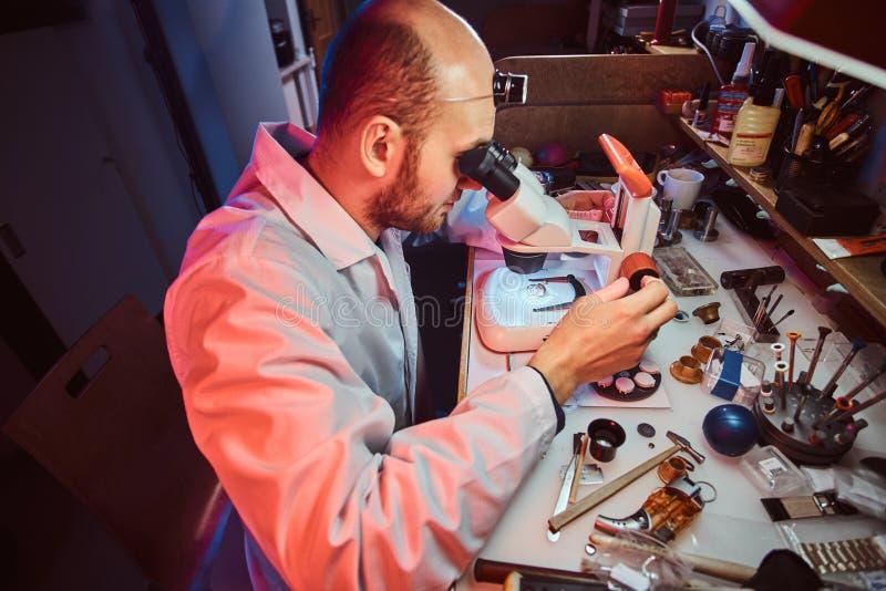 De ernstige horlogemaker herstelt cutomer orde bij zijn eigen het herstellen studio stock foto