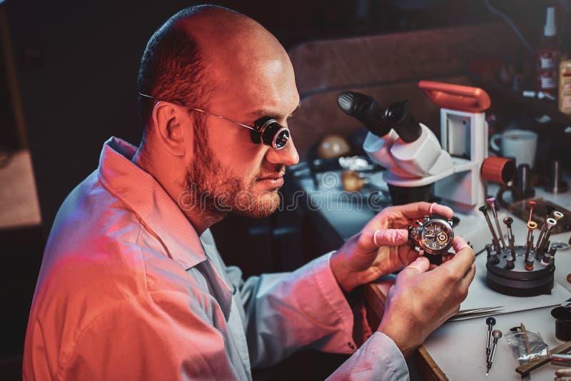 De ernstige horlogemaker herstelt cutomer orde bij zijn eigen het herstellen studio stock afbeeldingen