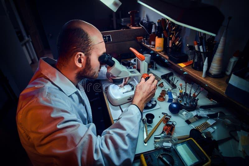 De ernstige horlogemaker herstelt cutomer orde bij zijn eigen het herstellen studio royalty-vrije stock afbeeldingen