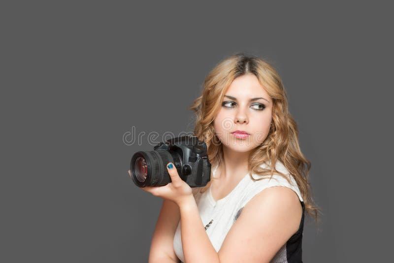 De ernstige jonge vrouw houdt een camera royalty-vrije stock afbeeldingen