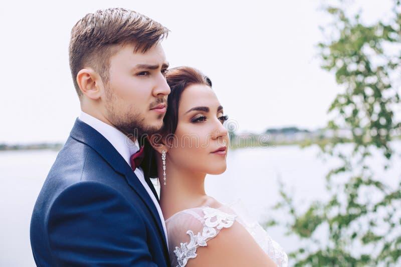 De ernstige jonggehuwden bevinden zich op de rivierbank stock foto's