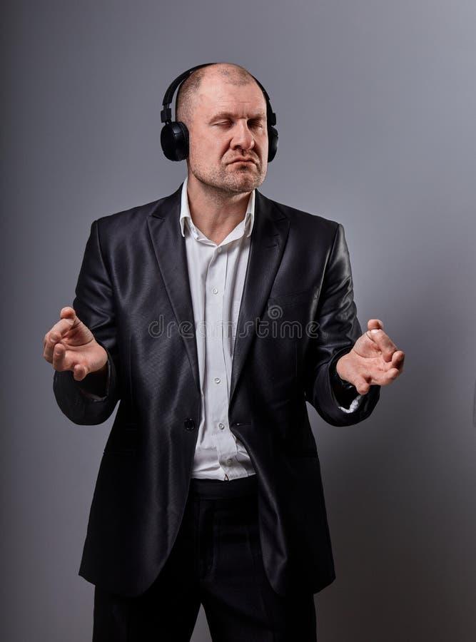De ernstige kalme emotionele dansende en zingende kale mens die de muziek in draadloze hoofdtelefoon en de handen tonen zen onder stock fotografie