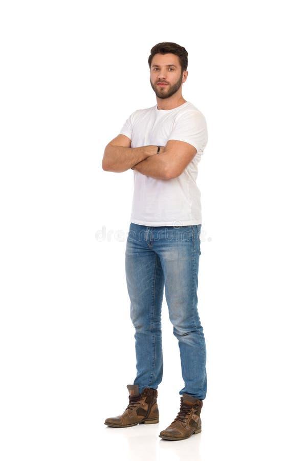De ernstige Knappe Mens in Jeans en Witte T-shirt bevindt zich met Gekruiste Wapens stock fotografie