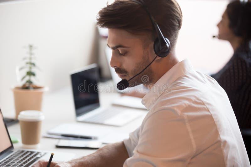 De ernstige mannelijke arbeider in hoofdtelefoon maakt nota's online raadplegend cli?nt royalty-vrije stock fotografie