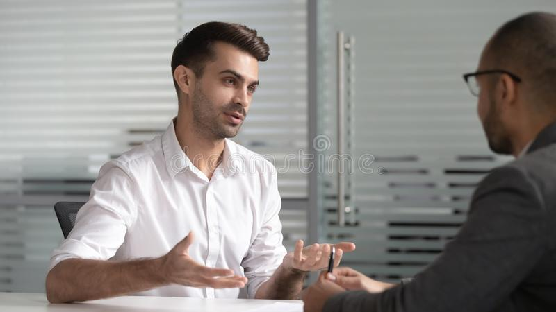 De ernstige mannelijke professionele verkoper raadpleegt klant op commerciële vergadering stock foto's