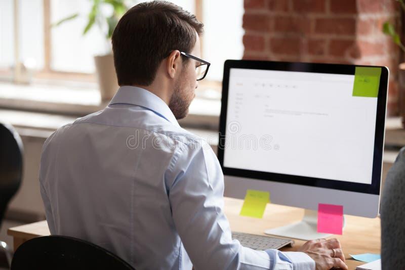 De ernstige mannelijke werknemer schrijft bedrijfsbrief aan cliënt royalty-vrije stock afbeeldingen
