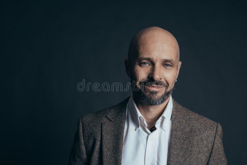 De ernstige mens op middelbare leeftijd met een glimlach gekleed in toevallig stelt op een donkergrijze achtergrond stock afbeeldingen