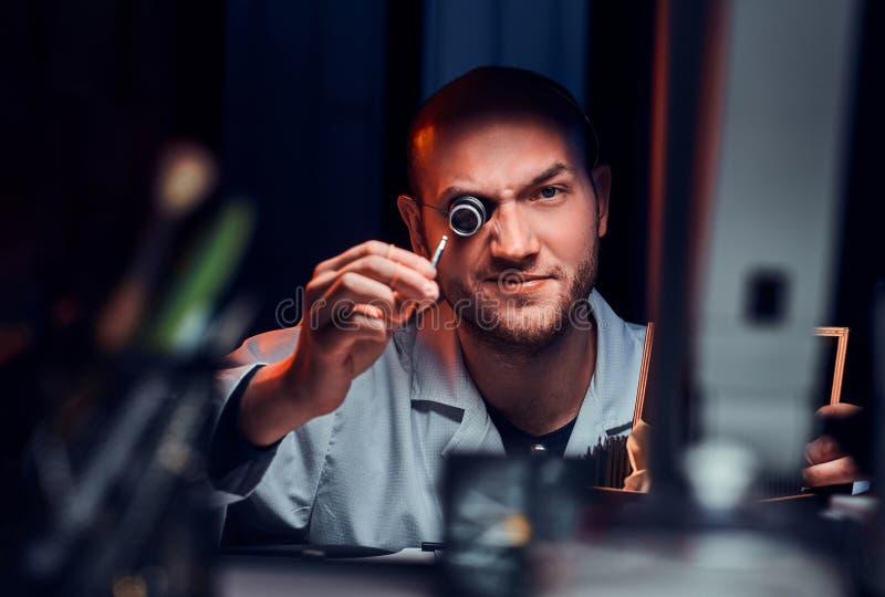 De ernstige mens stelt voor fotograaf bij zijn werkplaats met monocle royalty-vrije stock afbeelding