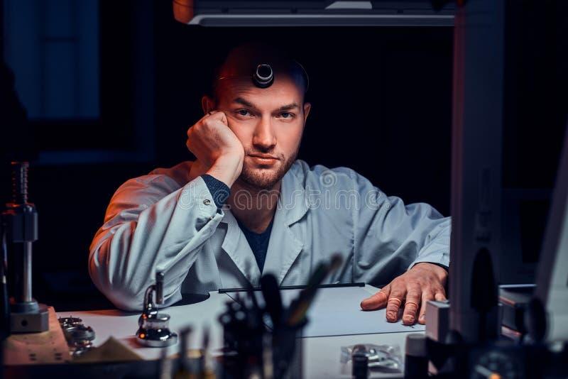 De ernstige mens stelt voor fotograaf bij zijn werkplaats met monocle royalty-vrije stock fotografie