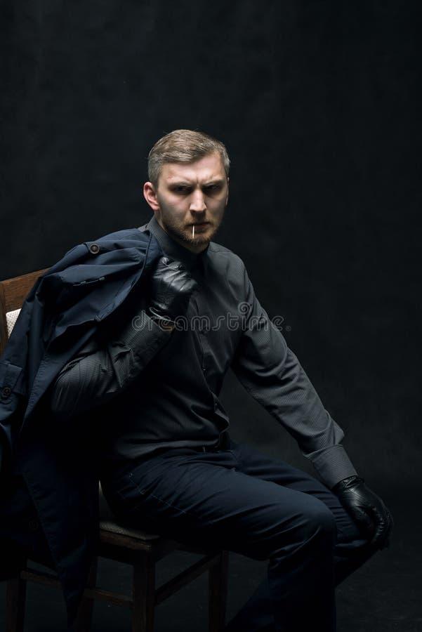 De ernstige mens in zwarte leerhandschoenen zit op een stoel royalty-vrije stock fotografie