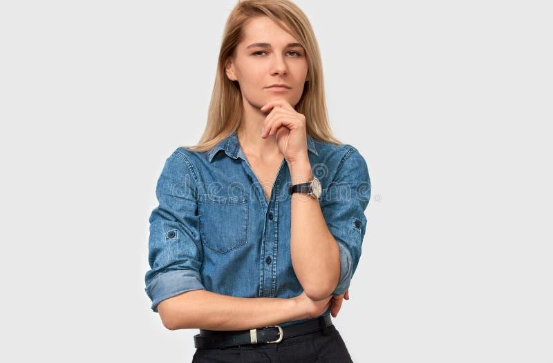 De ernstige mooie blonde jonge vrouw die denimoverhemd met vinger dragen vouwde op de kin die haar gezicht fronsen en aan de came royalty-vrije stock afbeeldingen