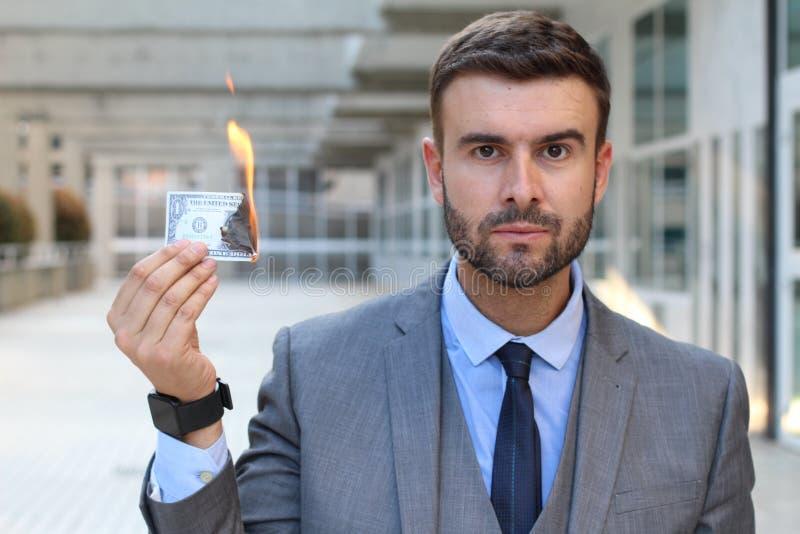 De ernstige rekening van de zakenman brandende dollar stock foto