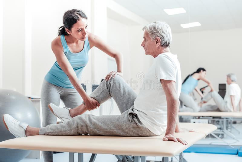 De ernstige trainer die oude gehandicapten uitrekken bemant benen royalty-vrije stock afbeeldingen