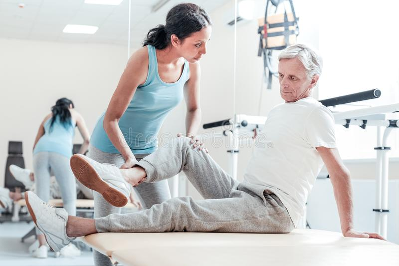De ernstige trainer die verlamd oud uitrekken bemant benen stock afbeeldingen