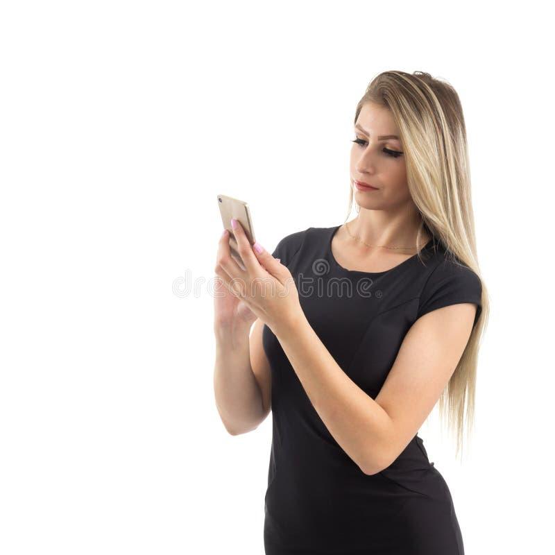 De ernstige vrouw gebruikt cellphone De blondepersoon draagt zwarte stock foto