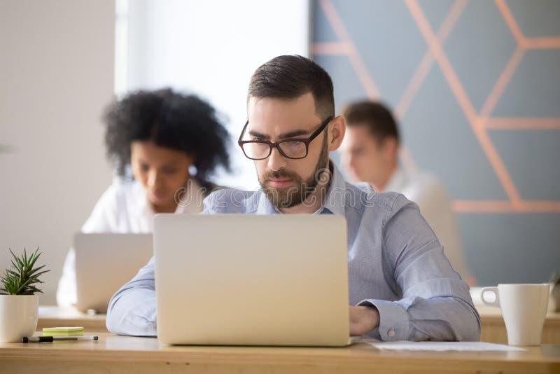 De ernstige zakenman concentreerde zich op het computer online werk in het coworking royalty-vrije stock afbeelding