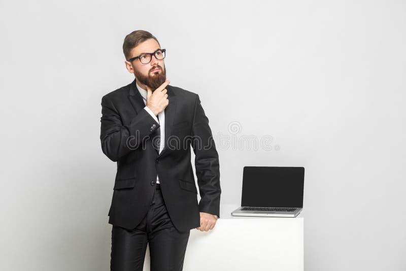 De ernstige zekere nadenkende gebaarde jonge zakenman in zwart kostuum bevindt zich dichtbij zijn werkende plaats en houdt zijn b royalty-vrije stock fotografie