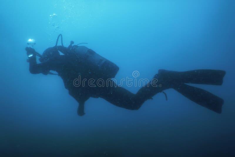 De Ertsader van scuba-duikerswimming underwater explores en onderzoekt Zeebedding royalty-vrije stock foto