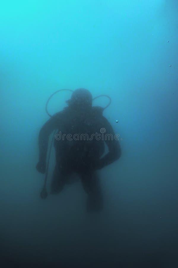 De Ertsader van scuba-duikerswimming underwater explores en onderzoekt Zeebedding stock afbeeldingen