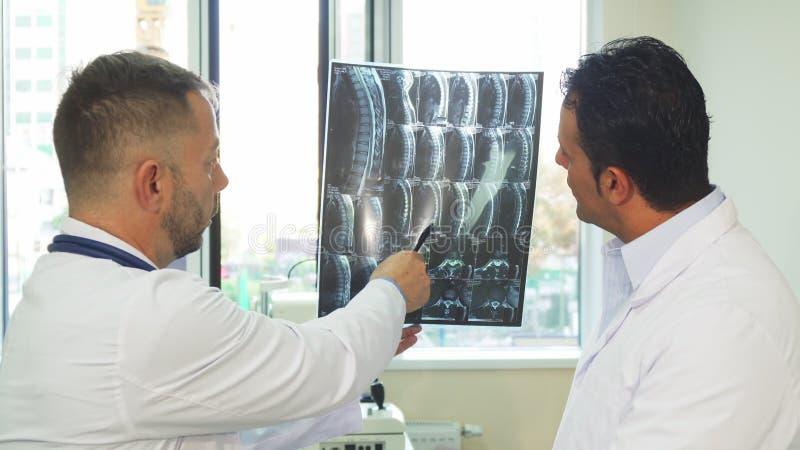De ervaren artsen bestuderen de Röntgenstraal van hun patiënt stock foto