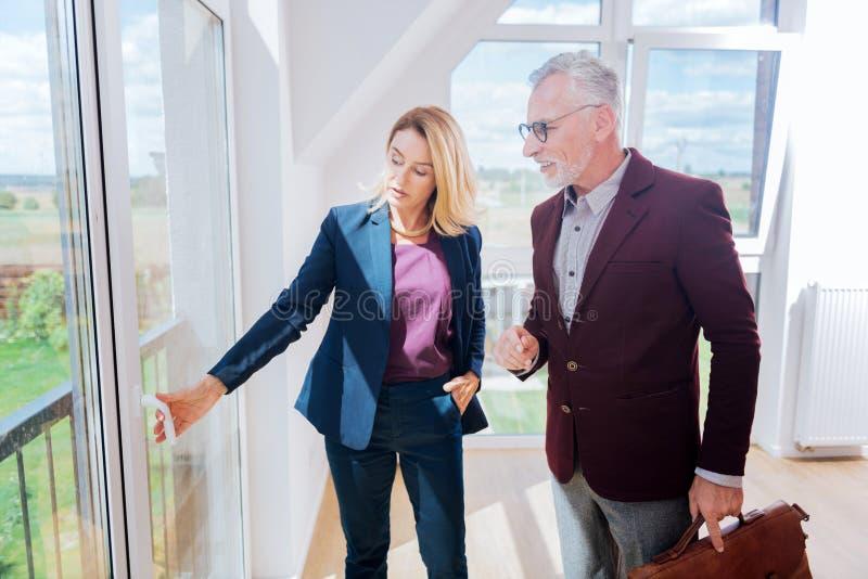 De ervaren vrouwelijke landgoedagent die venster tonen bekijkt haar rijke cliënt stock afbeeldingen