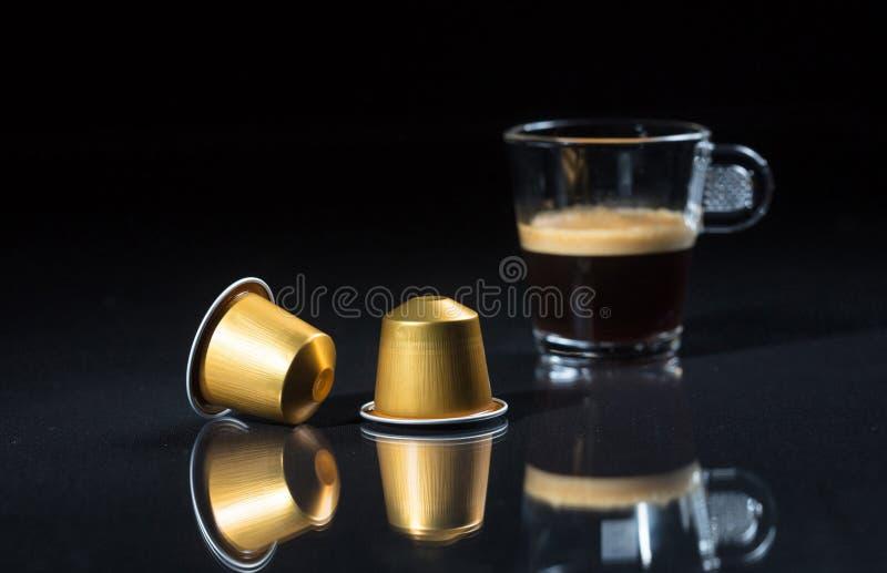 De de espressocapsules en koffie vormen op zwarte achtergrond, Close-upmening met details tot een kom stock foto