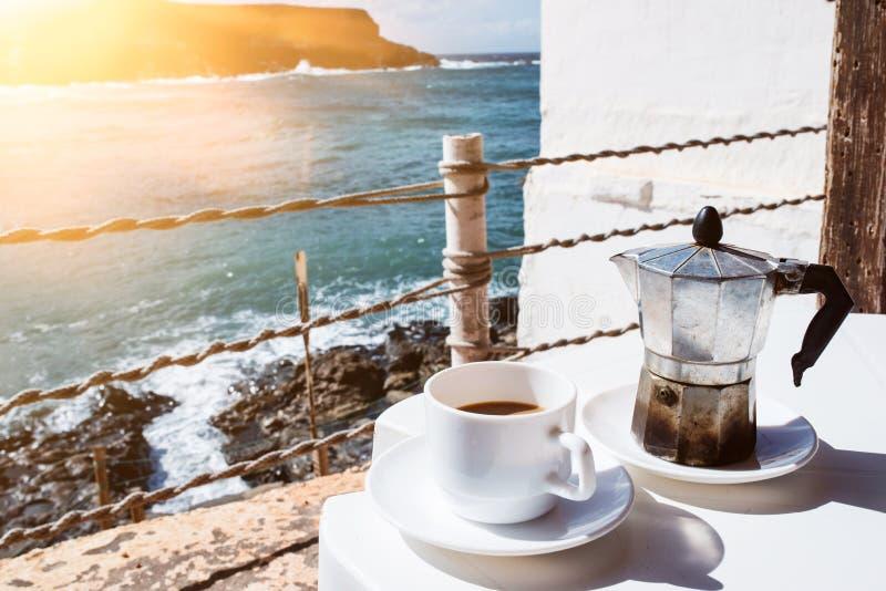 De espressomaker van de Mokapot en kop van koffie op lijst met kustlijn en oceaan op achtergrond royalty-vrije stock afbeelding