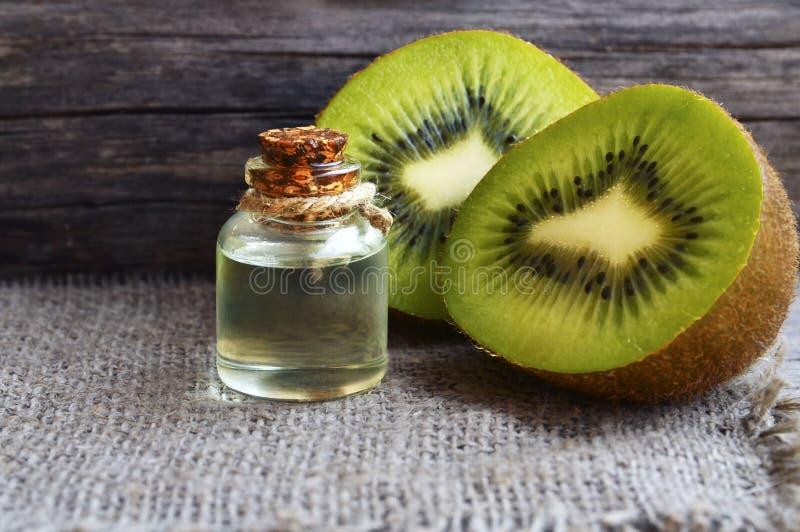 De essentiële die olie van het kiwizaad in een glaskruik met vers kiwifruit op oude houten achtergrond wordt gehalveerd Aromather stock afbeeldingen
