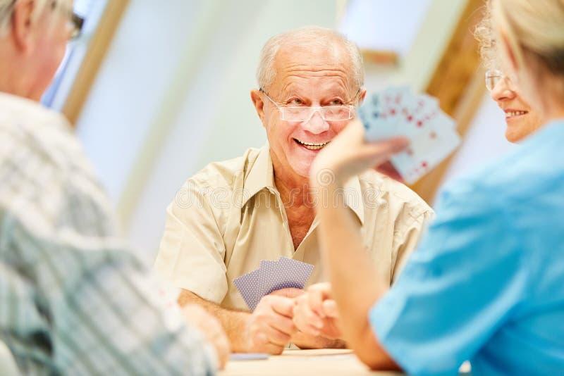 De essentiële oudsten genieten van speelkaarten stock foto's