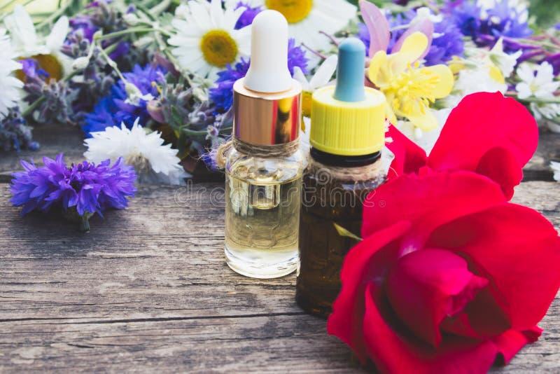 De etherische olie met nam in een glasfles toe dichtbij wildflowers op houten achtergrond stock fotografie