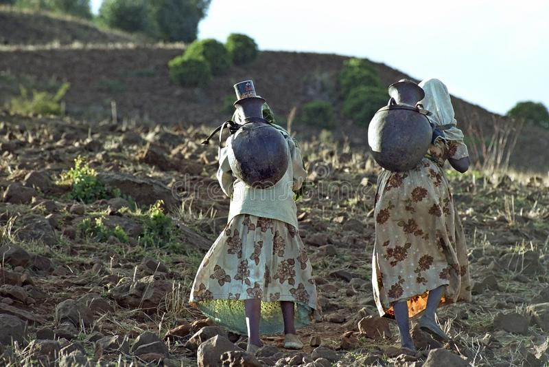 De Ethiopische vrouwen trekken drinkwater in bergen royalty-vrije stock afbeelding