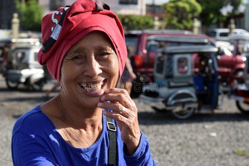 De etnische rijpe vrouw glimlacht aangezien zij voor aalmoes bij oude kerkyard bedelt Sluit omhoog stock fotografie