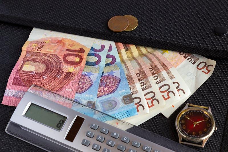 De euro bankbiljetten, de calculator en de klok liggen op de zwarte omslag voor stock foto's